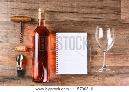 A high angle view of a wine bottle tasting notes notebook, cork screw, and wine glass on a wood table.
