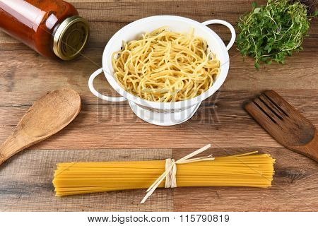 Still life of dried spaghetti, cooked pasta in a colander, a jar of sauce, herbs and wood utensils.