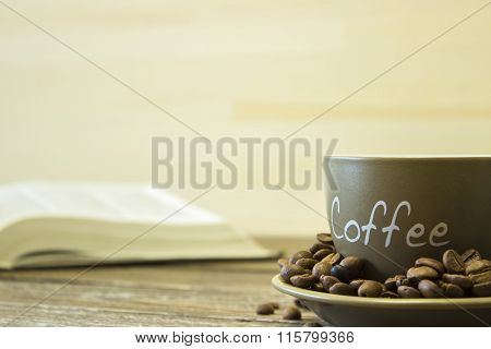 A Cup Of Coffee With Beans On The Background Of A  Book.