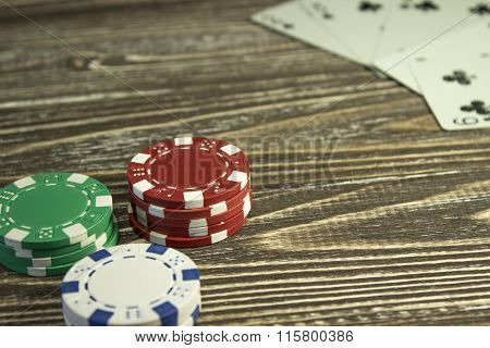 Poker Chips And Playing Cards On The Table. Focus On Red Chips