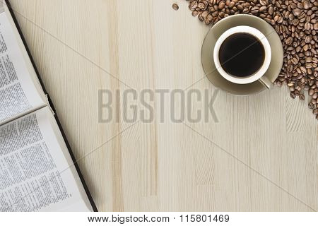 A Cup Of Coffee With Coffee Beans And A Book On A Wooden Table.