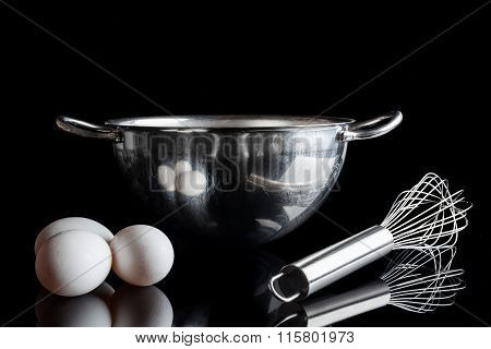 Steel bowl whisker eggs from side on black