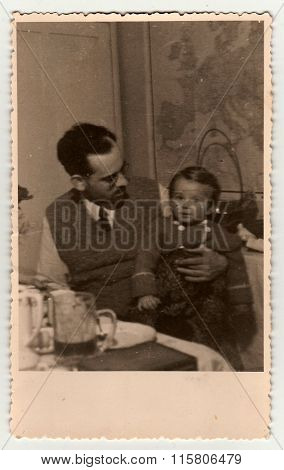 A vintage photo shows father with small girl.