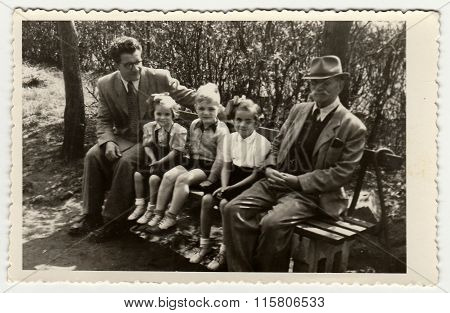 A vintage photo shows men with children. They sit on a bench.