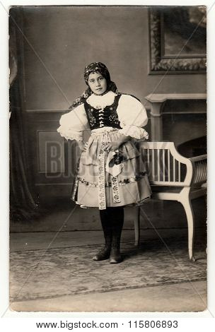 Vintage portrait photo shows girl in folk costum. Photo studio portrait circa 1930s.