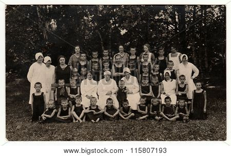 Vintage photo shows a group of boys and nurses in nature. Photo was taken in sanatorium circa 1940s.