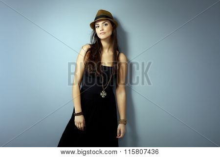 Attractive young woman standing against grey wall in black dress and straw hat.