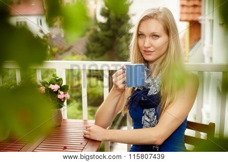 Portrait of young nordic woman sitting at balcony, drinking tea, looking away.