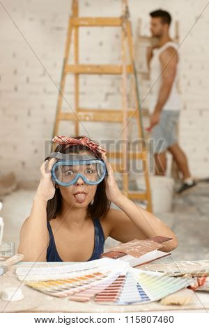 Playful woman sticking tongue, wearing protective eyewear at home renovation.