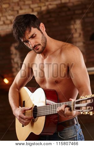 Romantic young man playing the guitar with bare upper body.