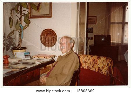 Vintage photo shows man sits on chair, circa 1980s.