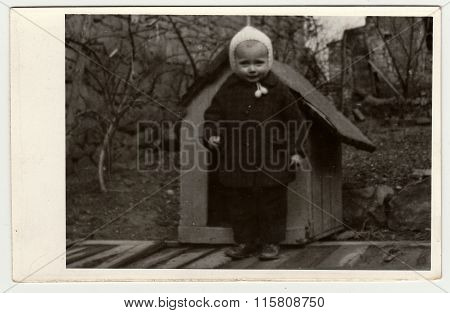 Vintage photo shows a small girl and kannel (doghouse), circa 1942.