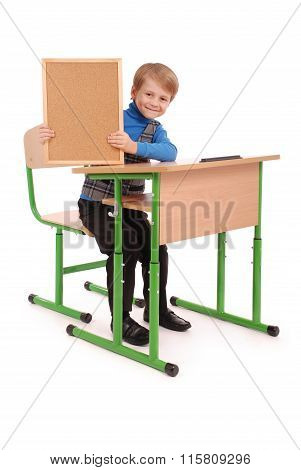 Boy Sitting At A School Desk And Holding Board