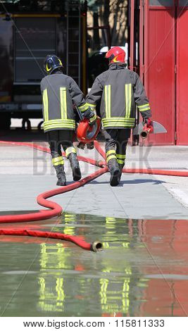 Two Firefighters Carry The Hydrant And Hose Pipes