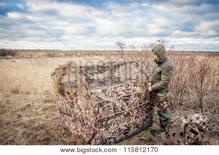 Man installing hunting tent in rural field