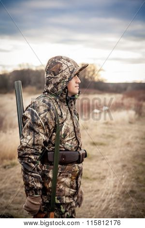 Hunter man with shotgun in camouflage standing in rural field during hunt
