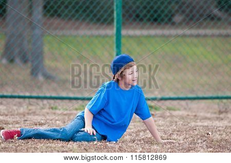 Young Boy With Baseball Hat Sitting In Grass