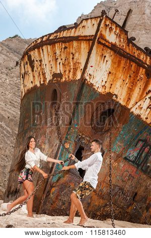 Young Couple In A Beach With Shipwreck