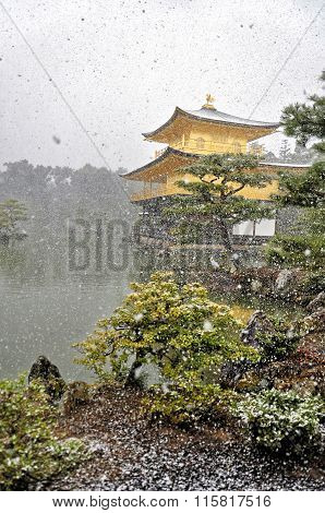 KYOTO, JAPAN - MARCH 10 2014 : Old Japanese golden castle, Kinkakuji Temple  in snow during winter.