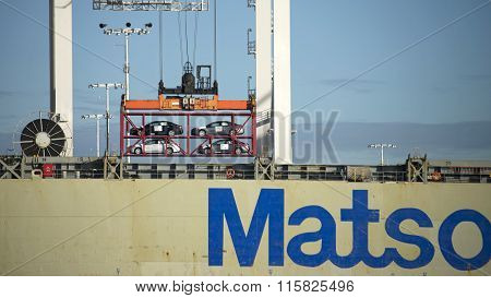 Cars in open shipping containers being loaded on Matson Cargo Ship MANOA