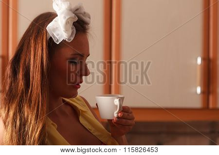 Pensive Pin Up Girl Drinking Tea Or Coffee At Home
