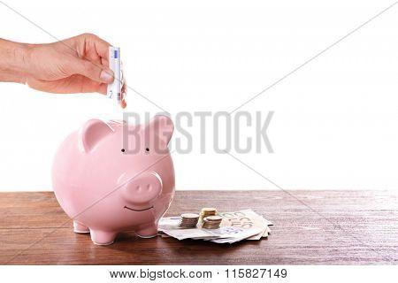Man putting Euro banknotes in pig moneybox