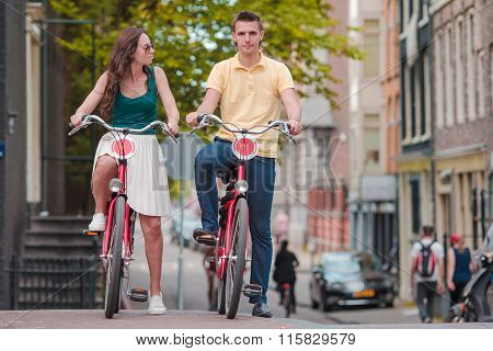 Young happy caucasian couple on bikes in old streets in Amsterdam
