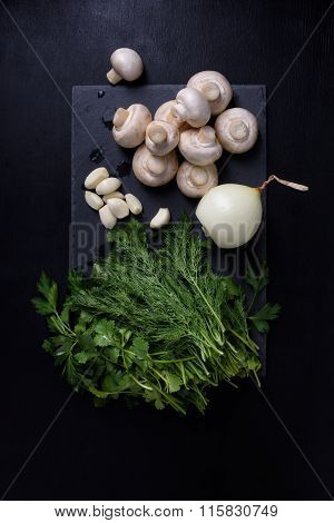 Young spring vegetables on slate board, black background. Champignons, garlic, dill. Flat lay.
