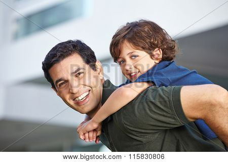 Happy child riding piggyback on his smiling father