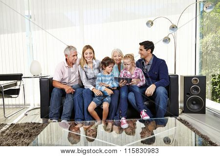 Big playing family with tablet PC in a living room