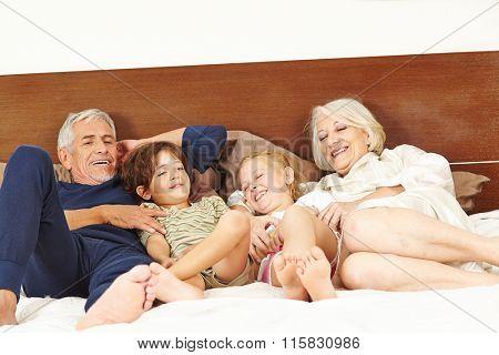 Grandparents tickling two grandchildren on bed in bedroom