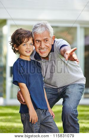 Senior in a garden pointing with his finger for his grandchild