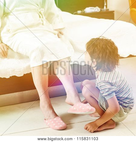 Grandson helping his grandmother at home in bedroom to put on slippers