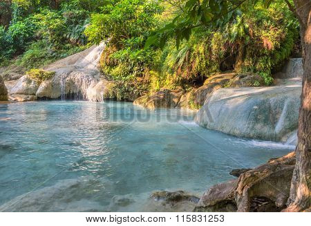 Jangle landscape with flowing turquoise water of seven step Erawan cascade waterfall at deep tropical rain forest. Erawan Falls National Park at Kanchanaburi, Thailand