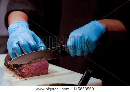 Butcher Cutting Medium Rare Beef On Cutting Board In The Kitchen