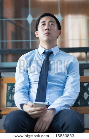 Asian Exhausted Businessman Sitting In Corporate Building