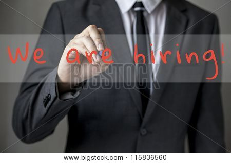 Businessman Writing 'we're Hiring' Tab On Virtual Screen