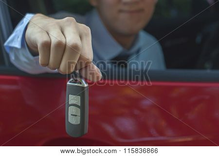 Young Asian Businessman Giving Out A Car Key Inside A Car (close-up)