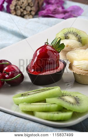Vertical image of variety of colorful mini tarts on plate.
