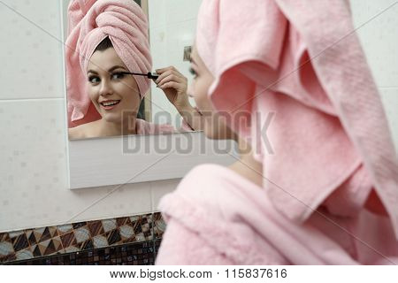 Image of smiling flirtatious woman using mascara