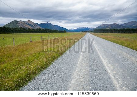 Straight gravel road through pasture in New Zealand with mountains in background