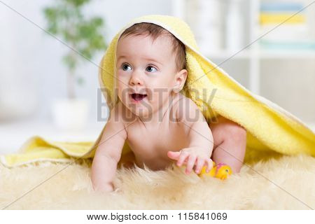 Funny baby kid under a hooded towel after bath