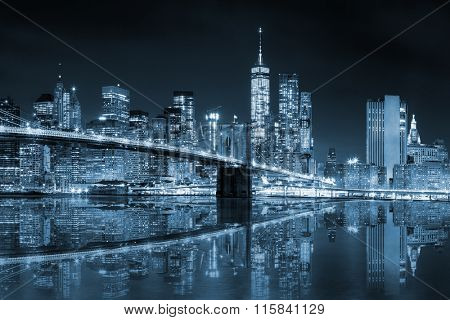 New York - Manhattan Skyline with skyscrapers and famous Brooklin Bridge by night with reflection, black and white blue toned