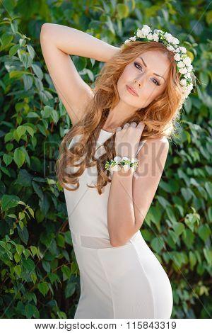 Portrait of a beautiful woman in a wreath of fresh flowers