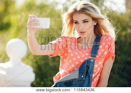 Summer portrait of beautiful woman making selfie