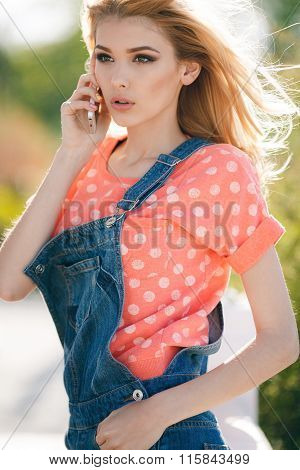 Summer portrait of a beautiful woman with mobile phone