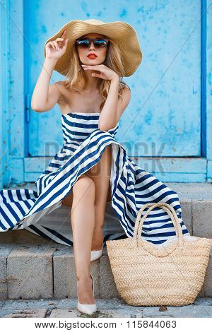 A woman in a straw hat sitting on the steps