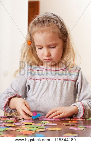 Child playing puzzle. Little girl play at home