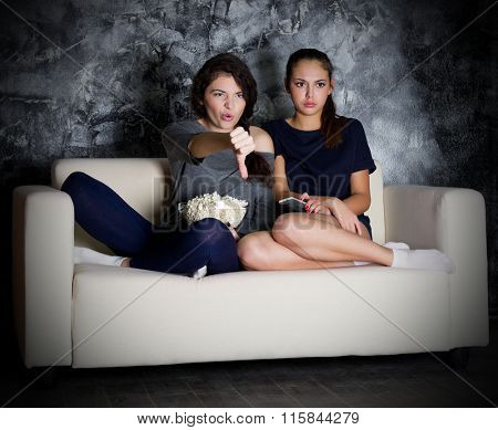 Two young girl looks TV at dark room