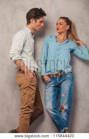 portrait of man with hands in pockets looking at his girfriend posing in studio while arranging her hair